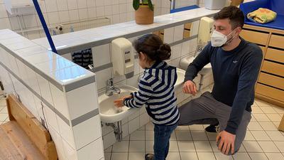 Erzieher Matthias Spengler der Kindertageseinrichtung Marienau in Achern beaufsichtigt ein Kind, das sich gerade die Hände wäscht.
