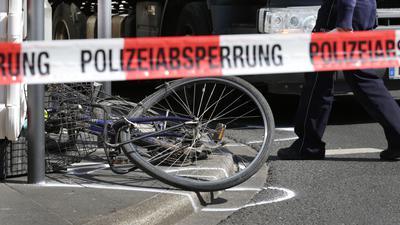 16.04.2019, Nordrhein-Westfalen, Düsseldorf: Hinter einem Absperrband mit der Aufschrift «Polizeiabsperrung» liegt am Unfallort ein Fahrrad vor einem Lastwagen. In der Düsseldorfer Innenstadt hat es einen Unfall mit einem Lastwagen (hinten) und einem Fahrradfahrer gegeben. Genauere Umstände zum Unfallhergang sind noch nicht bekannt. Foto: Martin Gerten/dpa +++ dpa-Bildfunk +++ | Verwendung weltweit