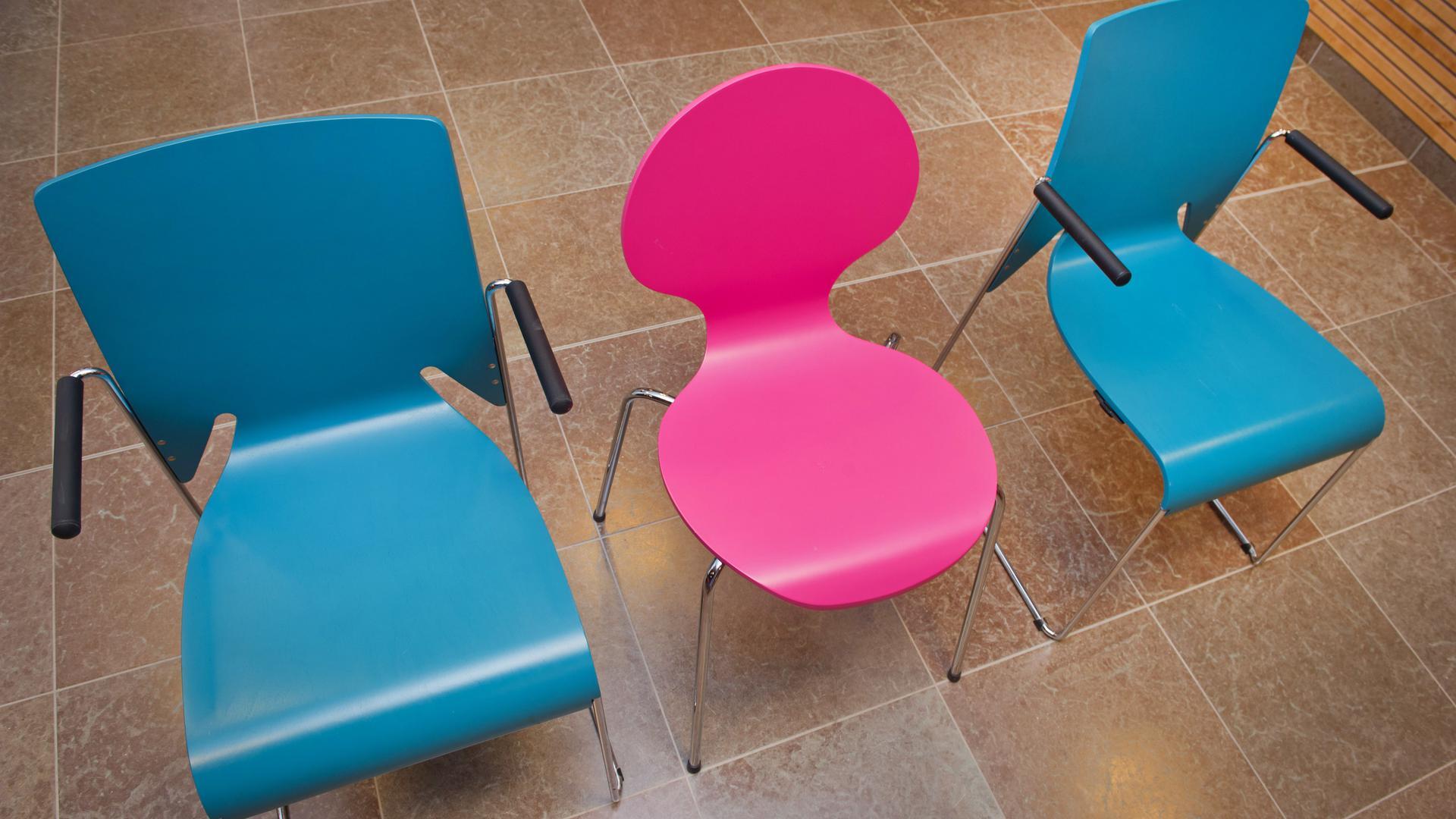 Stühle in unterschiedlicher Form und Farbe stehen in einem Konferenzraum.