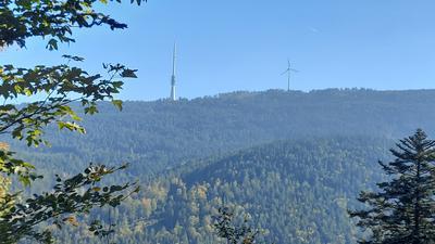 Ein bewaldeter flacher Berg, auf dem ein Fernsehturm und eine Windkraftanlage stehen.