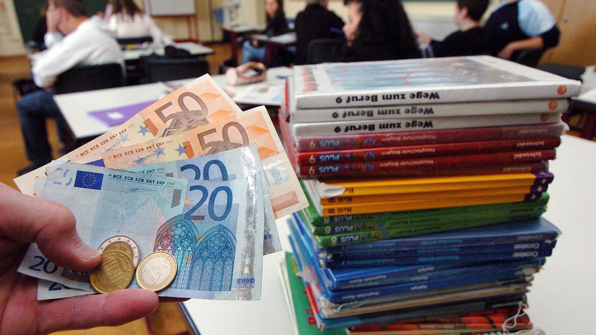 ARCHIV - Geld wird im Klassenzimmer einer Schule im niederbayerischen Straubing neben einem Stapel mit Schulbüchern gehalten (Illustration zum Thema Lernmittelfreiheit vom 24.09.2004). Das Büchergeld im Freistaat wird zum kommenden Schuljahr 2008/2009 abgeschafft. Das hat das Kabinett am Dienstag (11.03.2008) in München beschlossen. Foto: Armin Weigel dpa/lby (zu lby 7322 vom 11.03.2008) +++(c) dpa - Bildfunk+++ | Verwendung weltweit