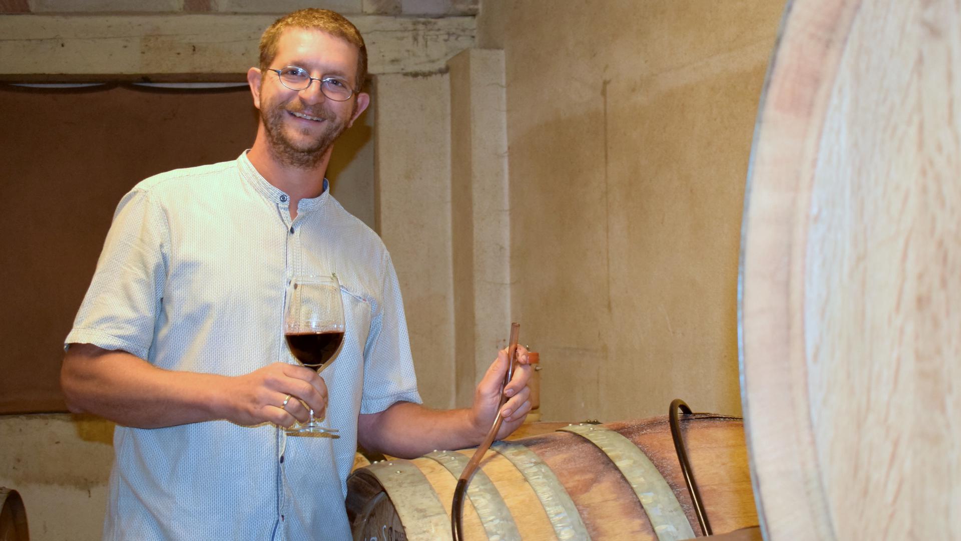 Ein junger Mann steht neben Holzfässern und hält ein Glas Rotwein in der Hand.