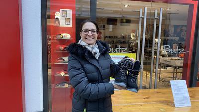 Miriam Schnell hält ein schwarzes Paar Winterschuhe hoch und hat diese beim Schuhhaus Butz in Achern gekauft.