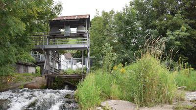 Wasser sprudelt unter einem Schütz mit Stahlaufbauten durch.