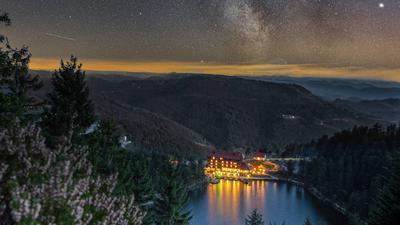 Hell erleuchtet von oben und unten ist der Mummelsee samt Hotel unter der Milchstraße.