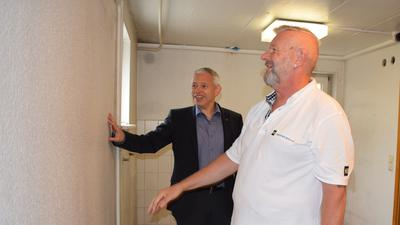 Ein Mann im Anzug und ein Mann in Malerkleidung stehen in einem Zimmer im Rohbauzustand.