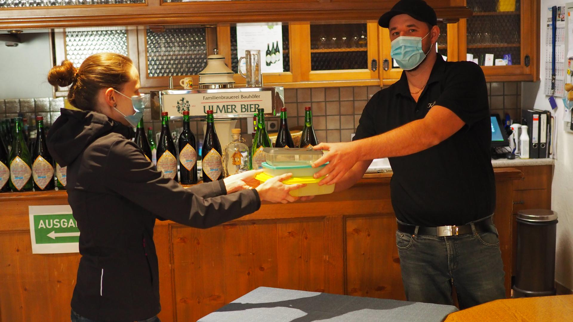 """Übergabestelle: So bekommen hier Kunden ihre bestellten Gerichten in mitgebrachten Behältern überreicht, zeigen Tobias Huber und Jasmin Weber von der """"Feldbachstube"""" in Oberachern."""