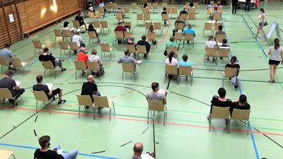 In einer Sporthalle sitzen Menschen auf Stühlen.