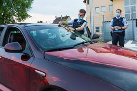 Zwei Polizeibeamte kontrollieren ein Fahrzeug.