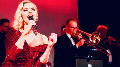 Rina Späth steht auf der Bühne mit einer Big Band im Hintergrund.