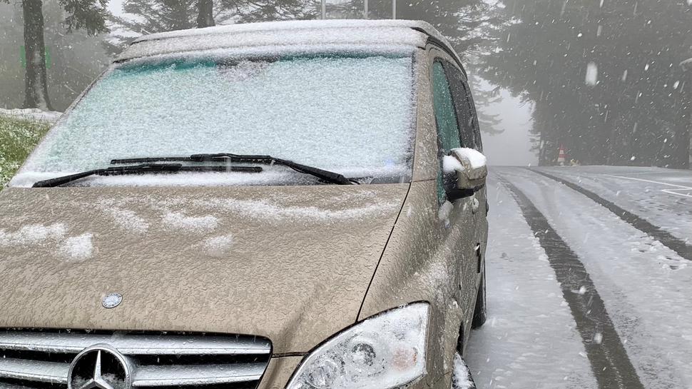 Ein parkendes Auto mit Schnee auf der Windschutzscheibe. Auch auf der Straße liegt eine dünne Schneeschicht.