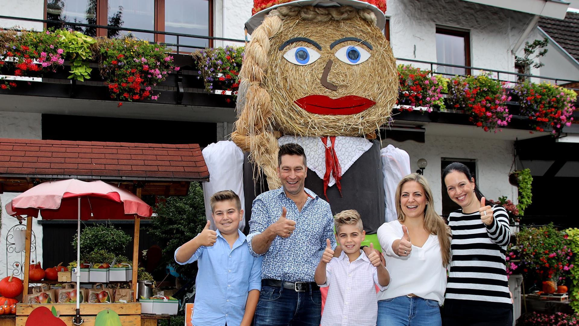 """Die ganze Familie freut sich über den ersten Platz bei """"Lecker aufs Land"""" – hier im Hof von Familie Weber vor der riesigen Strohpuppe Nadine"""