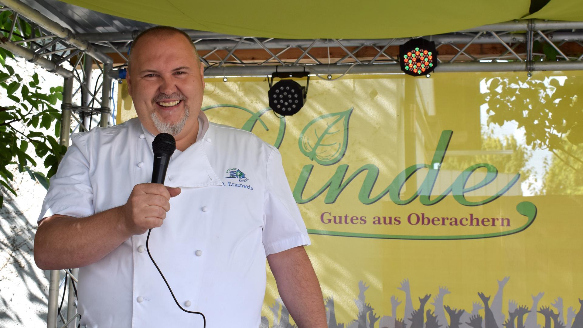 Ein Mann in einer Kochjacke steht mit Mikrofon auf einer Bühne.
