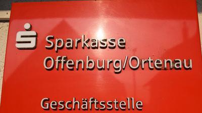 """Ein rotes Firmenschild mit der Aufschrift """"Sparkasse Offenburg/Ortenau"""" an einer Hauswand."""