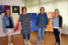 Vier Frauen stehen in einem großen Raum. Sie sind bunt angezogen und lächeln.