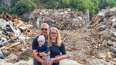 """Carola und Karl-Peter Kempen, hier mit ihrem Söhnchen Lukas, stehen vor den Trümmern ihrer Existenz. Das ist alles, was nach dem Ahr-Hochwasser von ihrem Hotel und Restaurant """"Jägerstübchen"""" in Mayschoß übrig geblieben ist."""