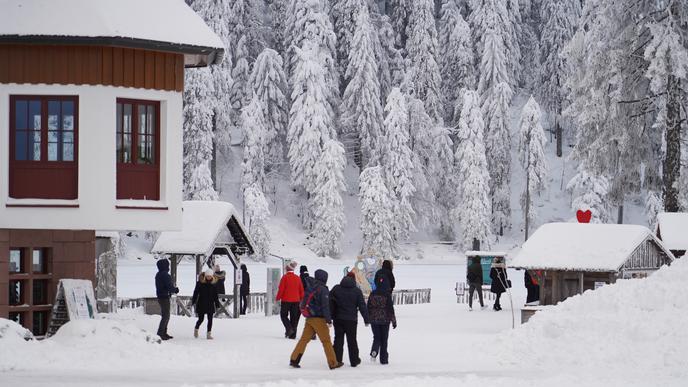 Winter-Ausflügler laufen durch den Schnee am Mummelsee.