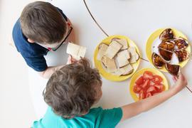 Zwei Kinder sitzen zum Frühstück in einem Kindergarten am Tisch und essen gemeinsam.