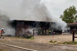 Rauch steigt aus einer Scheune in Achern, Feuerwehrleute stehen davor.