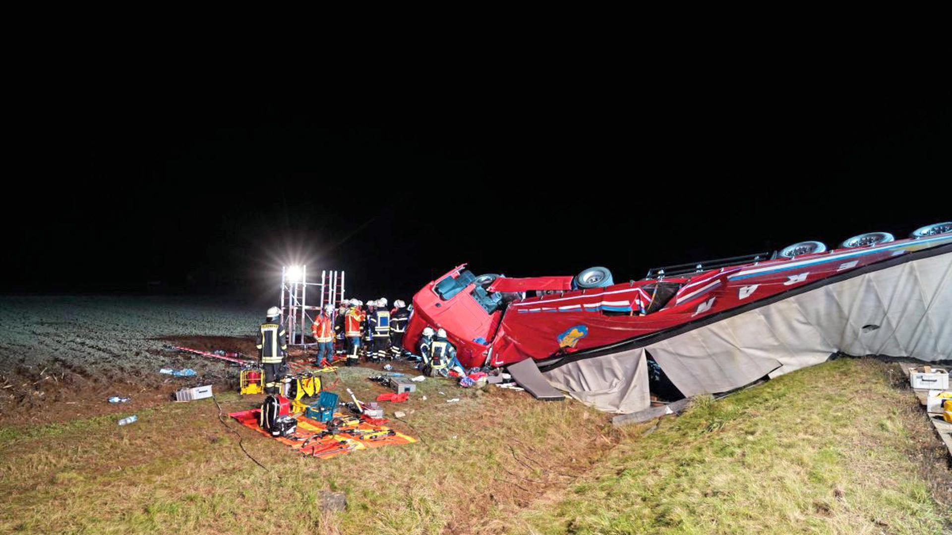 Rettungskräfte sind dabei, den Lkw-Fahrer nach dem Unfall auf der A5 bei Achern zu bergen.