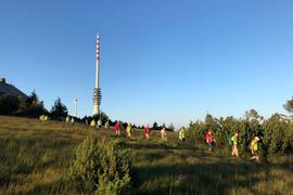 Wanderer in Hochmoor mit Turm im Hindergrund