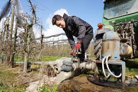 Jung-Obstbauer Maximilian Kammerer schließt eine Pumpe an einen Traktor an.