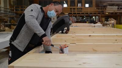 Manfred Nock und Victor Wolf (v.l.) von Burkart Haus in Renchen bauen einen Rahmen für ein Holzhaus.