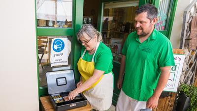Maria und Thomas Huschle stehen vor einer Hofladenkasse für Selbstbediener.