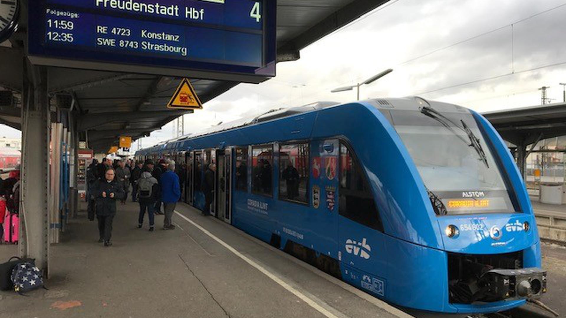 Ein blauer Wasserstoffzug steht an einem Bahnsteig.