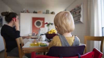 Ein kleines Kind sitzt in einem Hochstuhl vor einem Tisch. Eine Frau sitzt dabei. Sie telefoniert und tippt gleichzeitig auf einem Laptop.