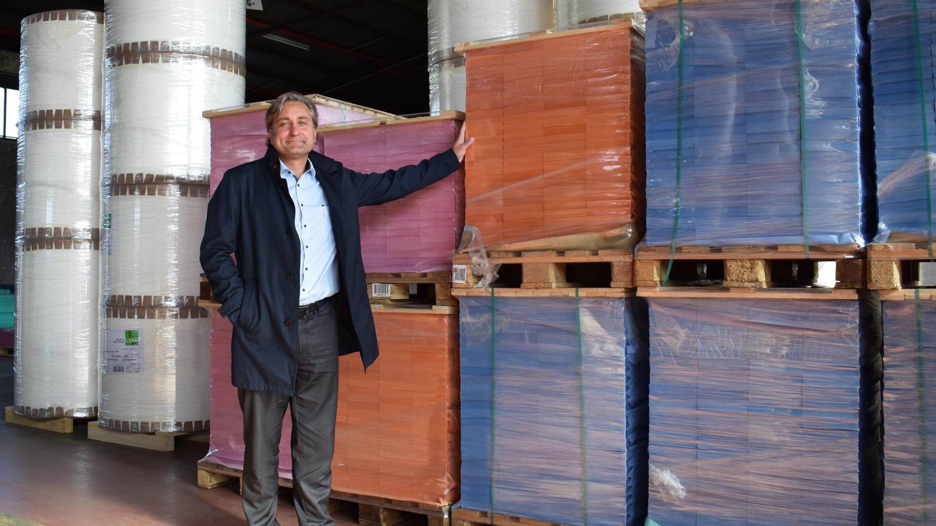 Ein Mann steht vor hohen Türmen aus Papierrollen und Paletten voller bunter Spezialpapiere.
