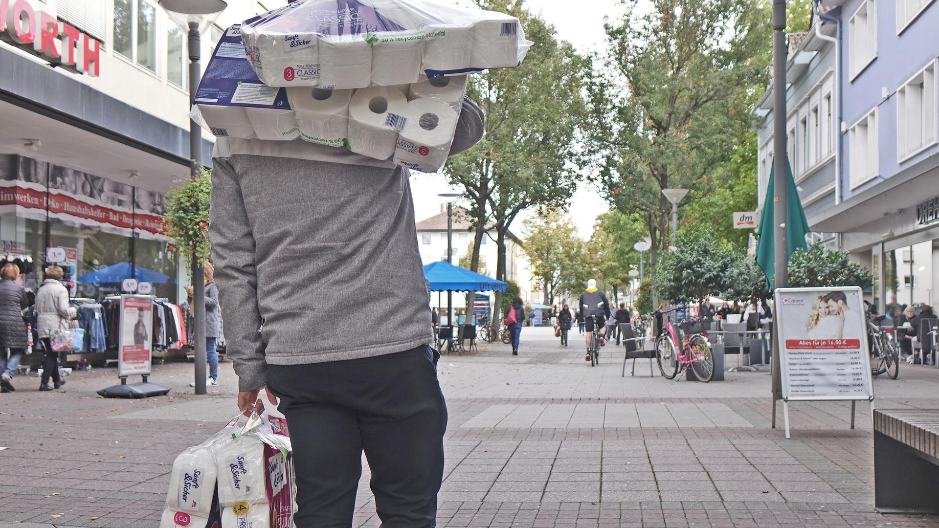 Ein Mann mit mehreren Packungen Toilettenpapier