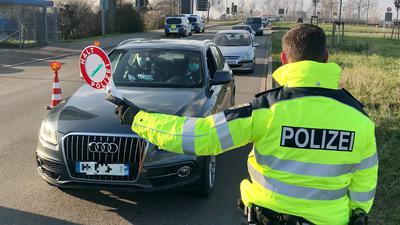 Ein Bundespolizist bringt am Kehler Grenzübergang an der Europabrücke ein Auto mit einer Warnkelle zum Stehen.