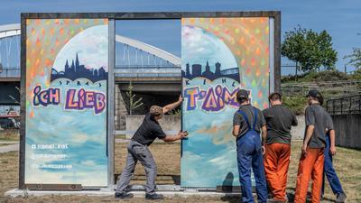 """""""Ich liebe dich"""" - """"Je t'aime"""": So heißt es auf der neu gestalteten Graffitiwand, die mit austauschbaren Platten konstruiert wurde."""