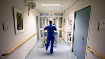Ein Krankenpfleger schiebt  in einer Klinik einKrankenbett durch den Flur.