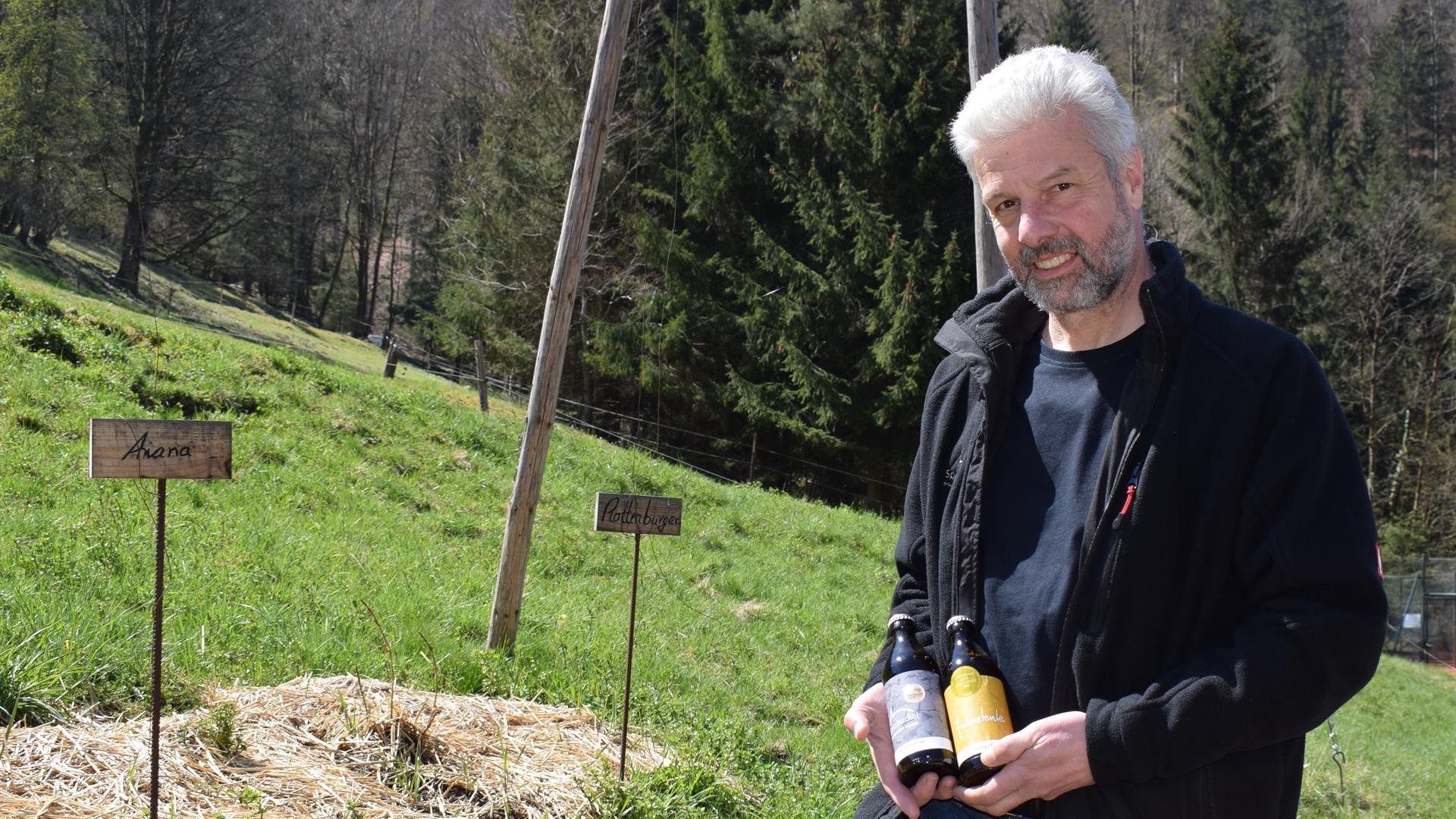 Ein schlanker Mann mit weißem Haar und grauem Vollbart steht im Grünen und hat zwei kleiner Bierflaschen in der Hand.