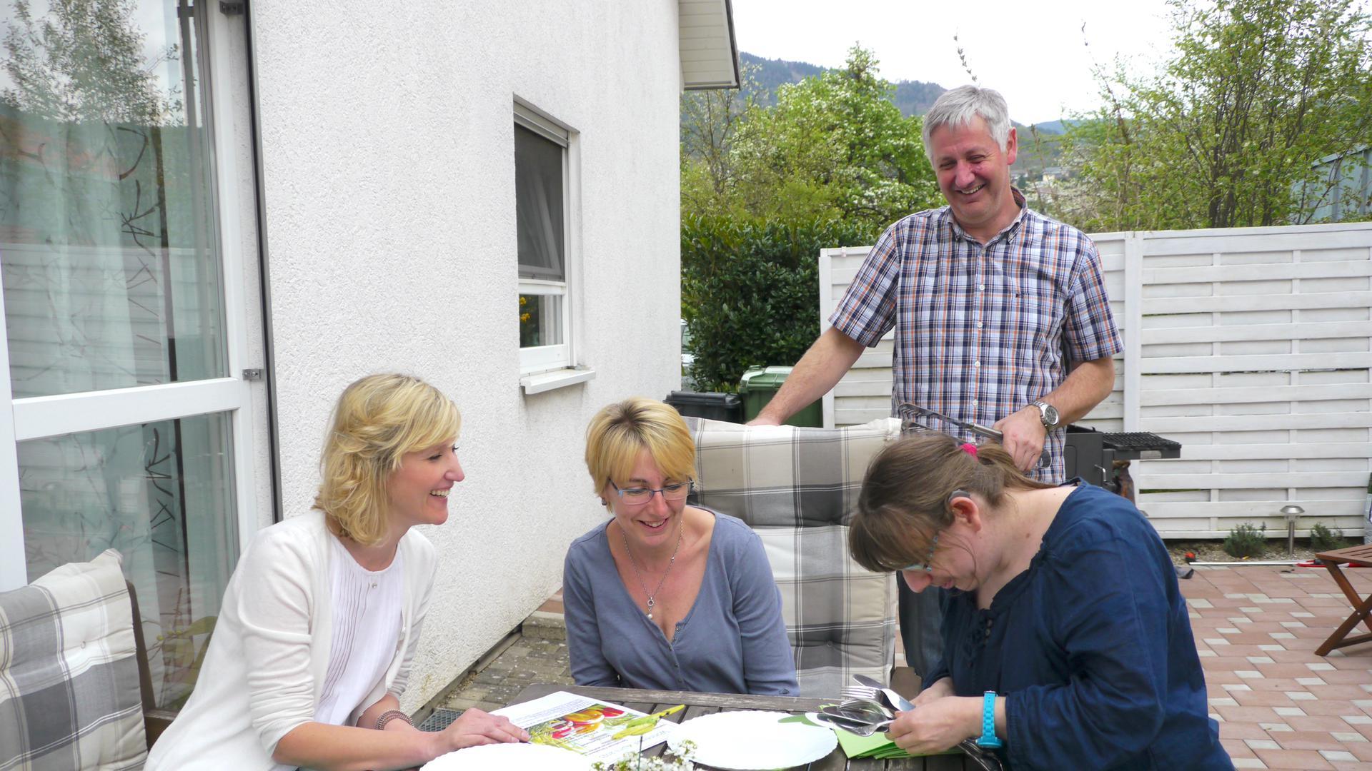 Eine Familie auf ihrer Terrasse. Sie lachen zusammen und decken den Tisch.