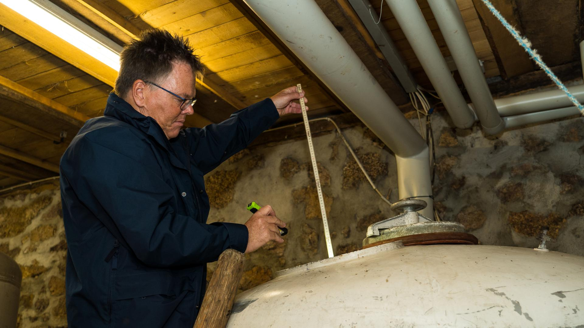 Zollamtsinspekteur Jan Frank misst mit einem Zollstock den Inhalt der Maischefässer im Keller des Oberkircher Schnapsbrenners Josef Brandstetter.