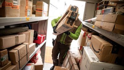 Ein Paketbote von UPS lädt Pakete in einen Transporter.
