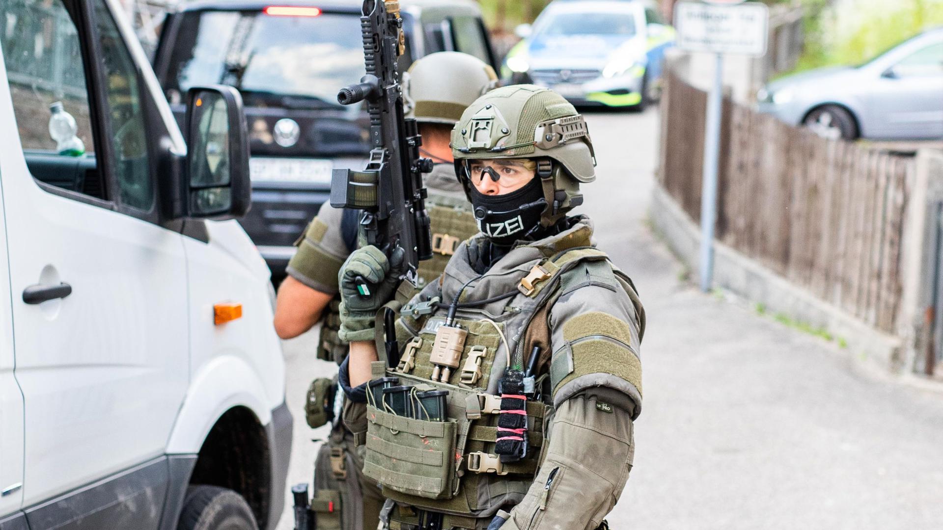 Polizisten des Sondereinsatzkommandos SEK stehen in einem Wohngebiet am Rand von Oppenau.