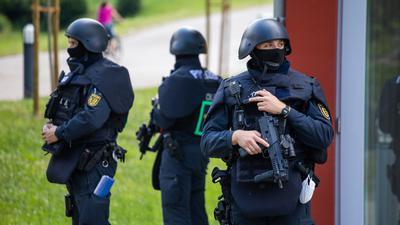 Beamte der Bereitschaftspolizei stehen vor der Mehrzweckhalle in Oppenau.