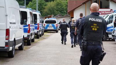 Oppenau: Polizisten gehen an einem Parkplatz an Polizeifahrzeugen vorbei. Am 12. Juli hatte ein Mann bei einer Kontrolle bei Oppenau Polizisten bedroht und entwaffnet und ist anschließend geflohen.