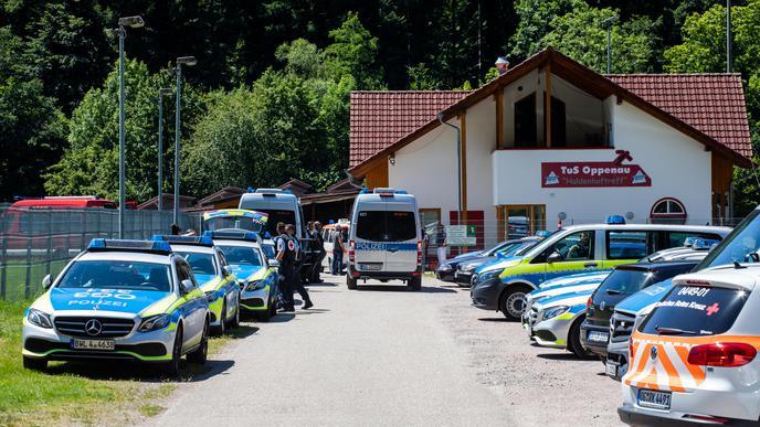 12.07.2020, Baden-Württemberg, Oppenau: Polizeifahrzeuge stehen auf einem Sammelplatz nahe der Gemeinde vor einem Sportlerheim. Ein mit Pfeilen und Bogen bewaffneter Mann hat in dem Ort im Schwarzwald Polizisten bedroht und ihnen die Waffen abgenommen. Anschließend flüchtete er in einen Wald und wird seither mit einem Großaufgebot gesucht. Foto: Philipp von Ditfurth/dpa +++ dpa-Bildfunk +++