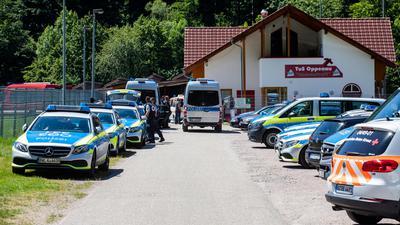 Polizeifahrzeuge stehen am 12. Juli auf einem Sammelplatz nahe Oppenau vor einem Sportlerheim.