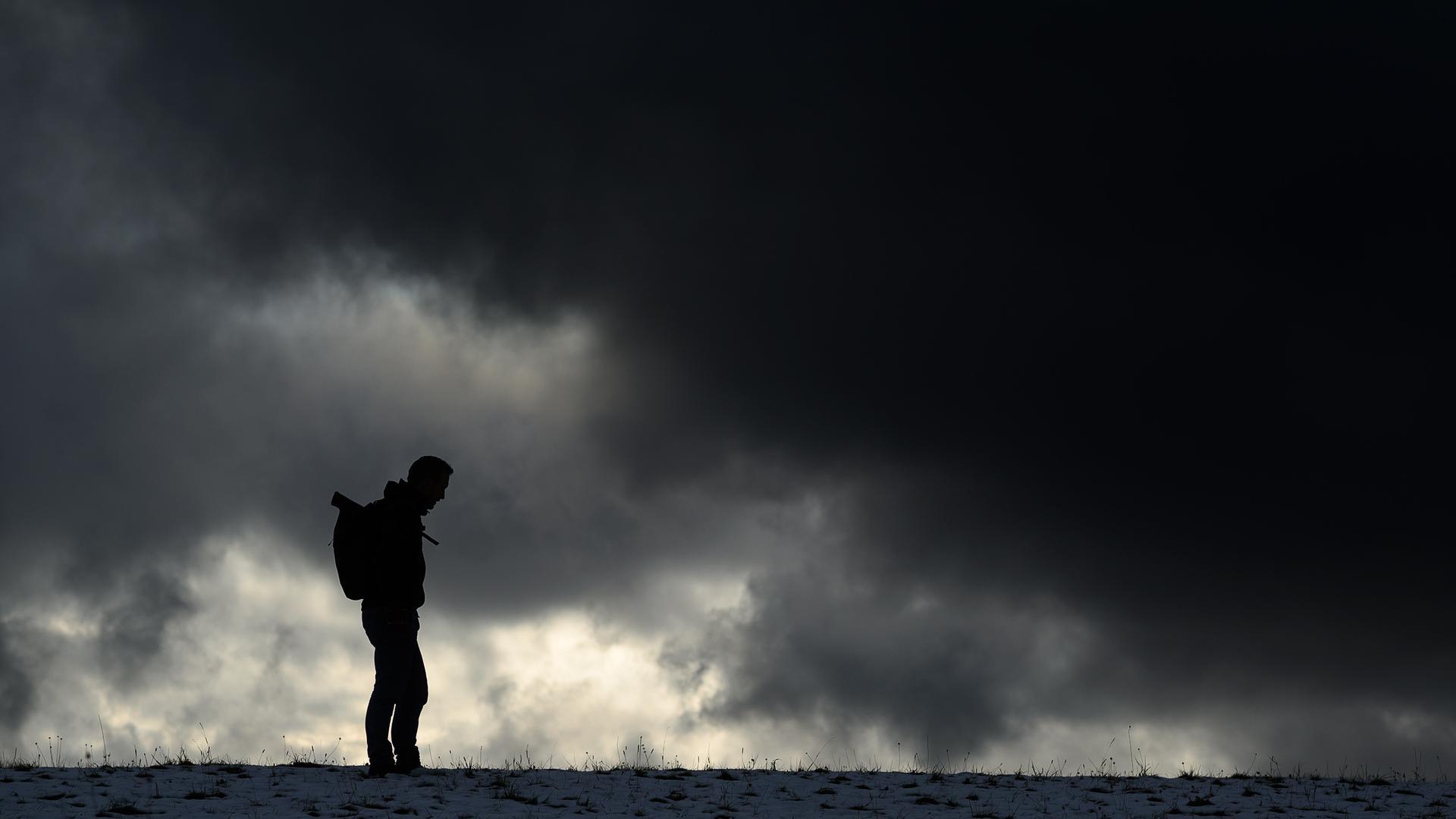 Ein Mann steht vor einem dunklen Himmel.