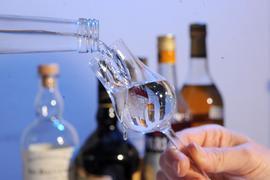 Ein Glas wird vor einer Ansammlung von Schnapsflaschen mit einem Obstbrand gefüllt.