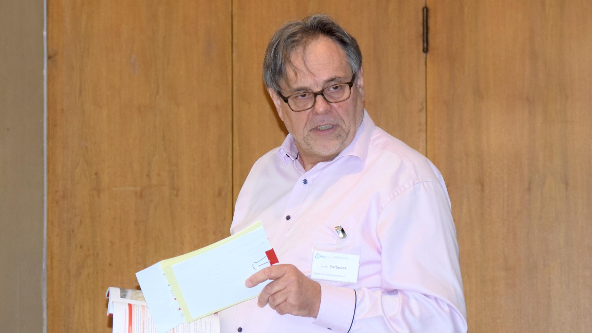 Ein Mann mit Brille hält Papiere in der Hand und spricht.