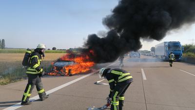Zwei Feuerwehrbeamte, einer davon mit Atemschutzmaske, vor einem brennenden Pkw mit starker Rauchentwicklung