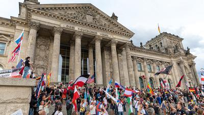 29.08.2020, Berlin: Teilnehmer einer Kundgebung gegen die Corona-Maßnahmen stehen auf den Stufen zum Reichstagsgebäude, zahlreiche Reichsflaggen sind zu sehen. Foto: Achille Abboud/NurPhoto/dpa +++ dpa-Bildfunk +++   Verwendung weltweit