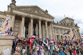 29.08.2020, Berlin: Teilnehmer einer Kundgebung gegen die Corona-Maßnahmen stehen auf den Stufen zum Reichstagsgebäude, zahlreiche Reichsflaggen sind zu sehen. Foto: Achille Abboud/NurPhoto/dpa +++ dpa-Bildfunk +++ | Verwendung weltweit